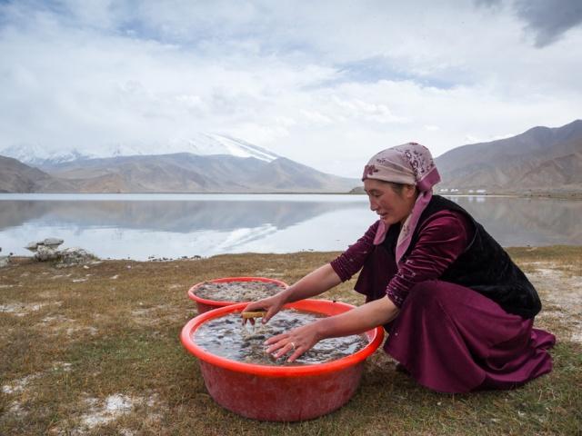 Женщина в национальном костюме моет шерсть около высокогорного озера Каракёль. Примечательно, что само озеро находится на территории Китая, но на его берегу есть два киргизских поселения, где сохранился традиционный уклад