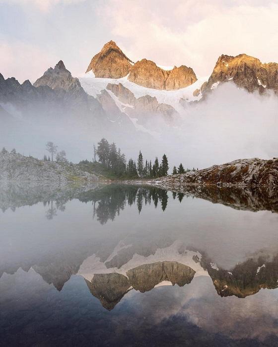 Огромная скала со снегом зеркально отражается в совершенно спокойной водной глади.