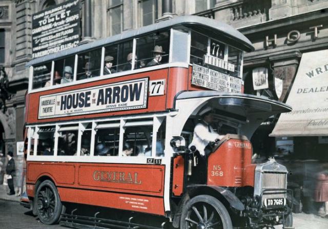 Двухэтажный лондонский автобус подбирает пассажира.