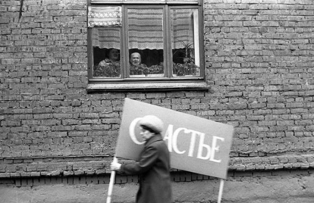 Женщина с плакатом спешит на первомайскую демонстрацию. СССР, Новокузнецк, 1 мая 1983 года.