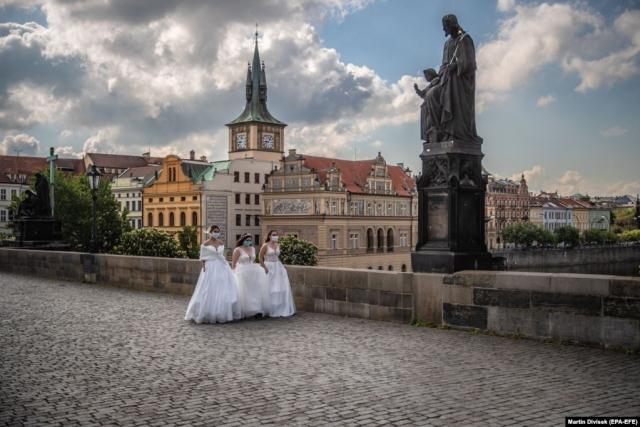 Модели в защитных масках и свадебных платьях гуляют Карловым мостом во время коммерческой съемки в Праге (Epa-EFE / Martin Divisek)