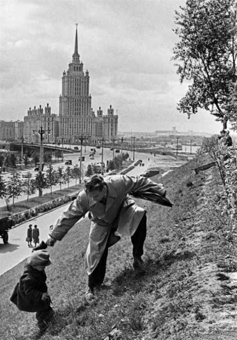 Отец помогает своему сыну подняться на вершину холма. СССР, Москва, 1972 год.